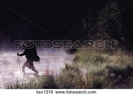 Stock Photograph of A man hiking through a misty Truckee River.