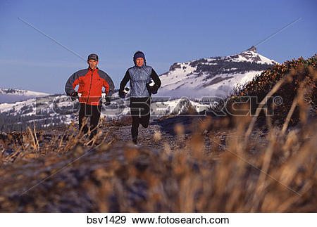 Stock Photograph of A couple trail running in the winter near.