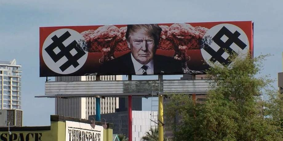 Artist trolls Trump with dollar swastika billboard.
