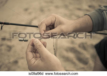 Stock Photography of Close up of fishermans hands preparing.