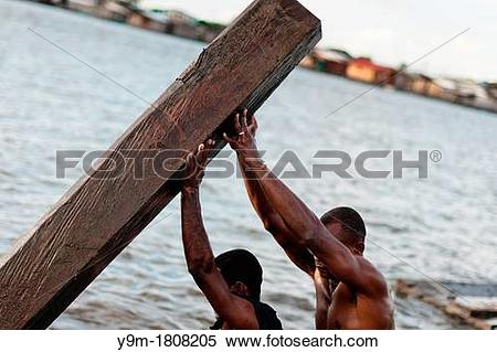Stock Image of Colombian workers lift a heavy timber from the.