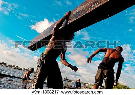 Picture of Colombian sawmill workers carry timbers from the.