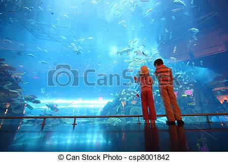 Stock Photo of little boy and girl standing in underwater aquarium.