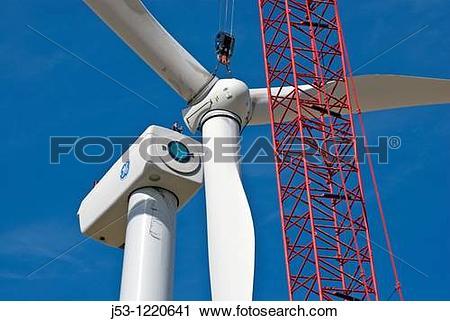Stock Photography of Crane lifting wind turbine rotor into.