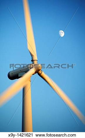 Stock Photography of Wind turbine rotors with blue sky and moon.