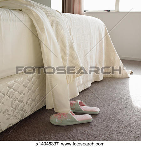 Picture of Slippers beside bed with sheets turned over x14045337.