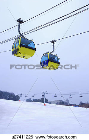 Stock Image of Two cable cars hanging in the mid.