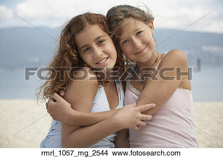 Stock Photo of Two teenage girls hugging at beach.