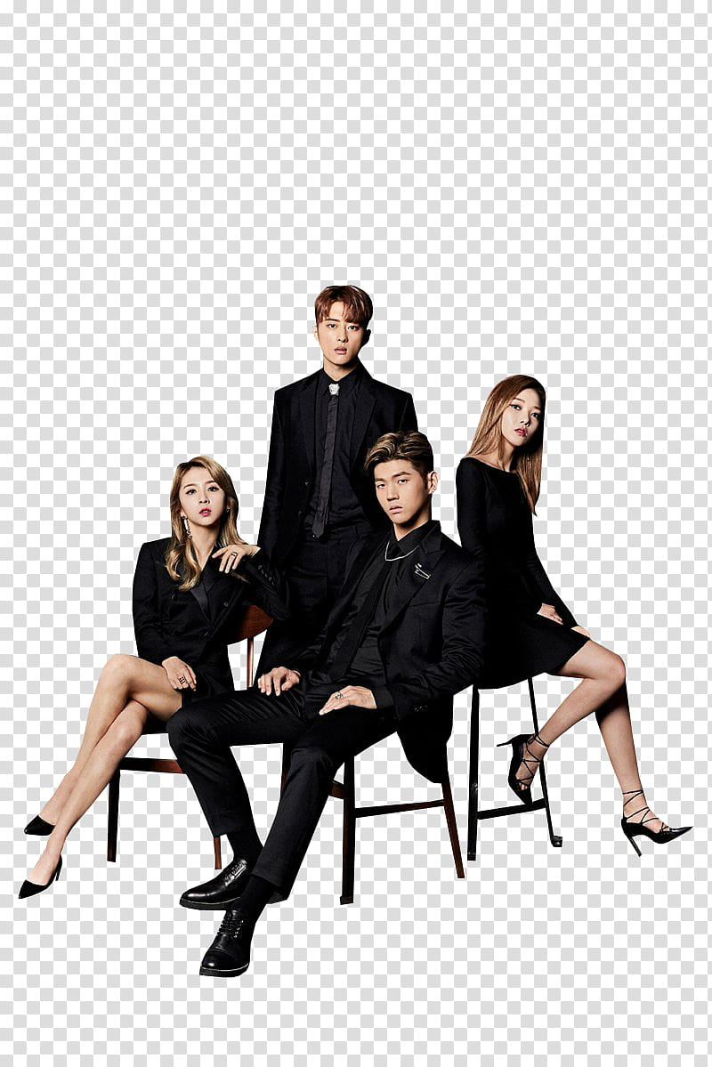 One man standing beside two women and one man sitting.