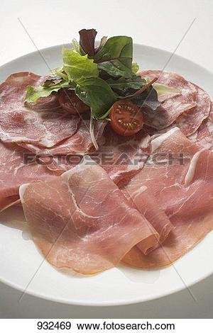 Stock Photograph of Various types of Italian ham with salad.