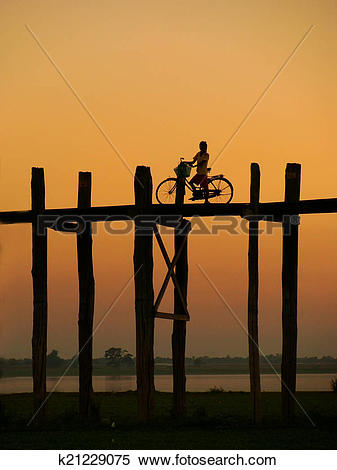 Stock Image of Silhouetted person on with a bike on U Bein Bridge.