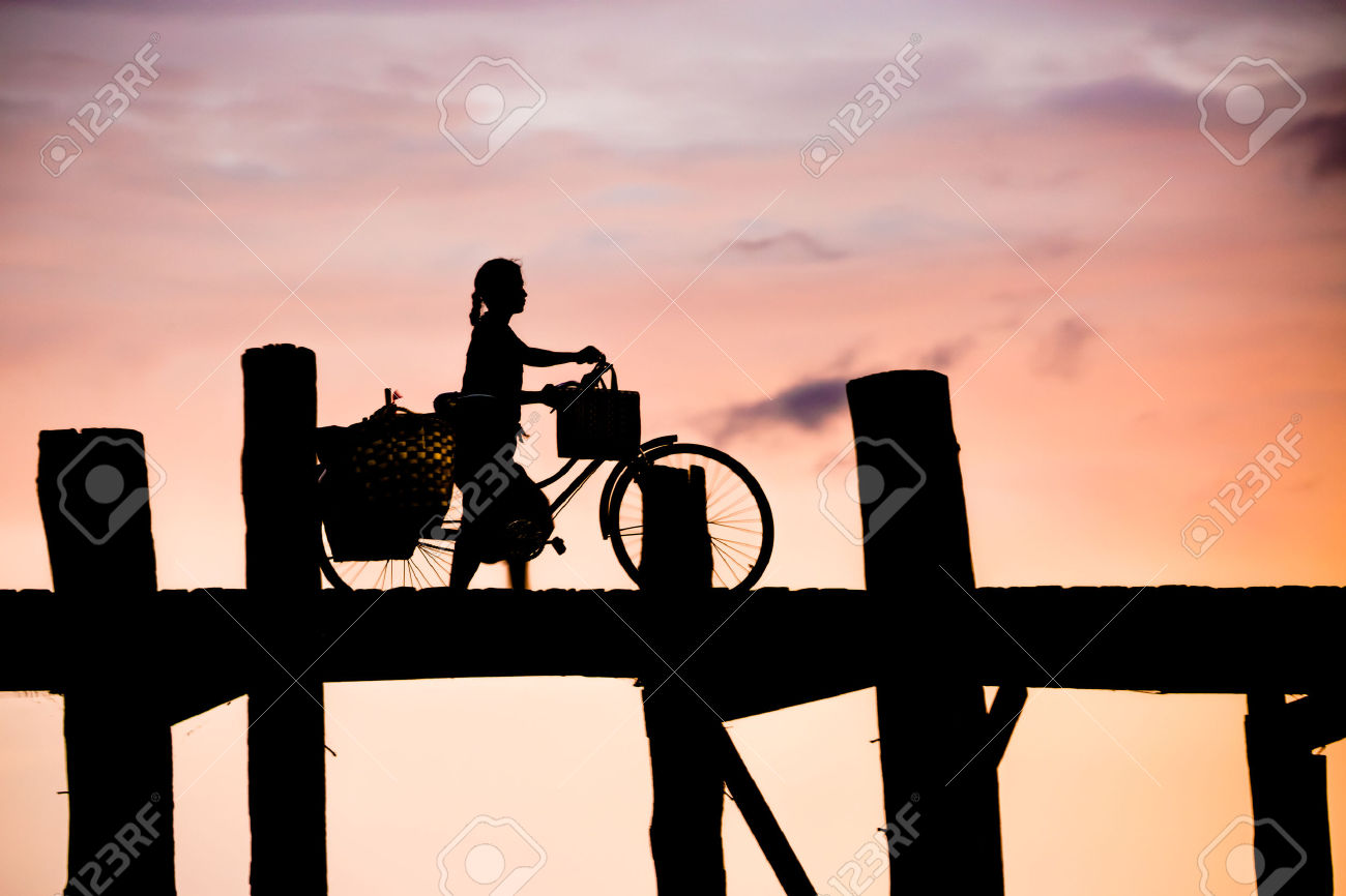 Silhouetted Person With A Bike On U Bein Bridge At Sunset.