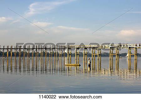 Stock Photo of A man fishing next to U Bein Bridge, Amarapura.