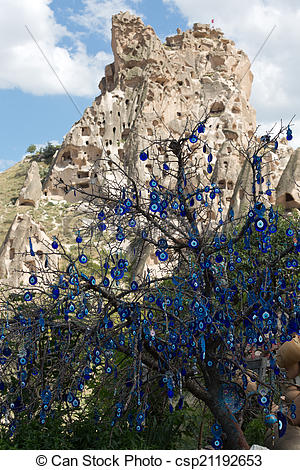 Stock Images of Evil eye in tree behind Uchisar Castle in.