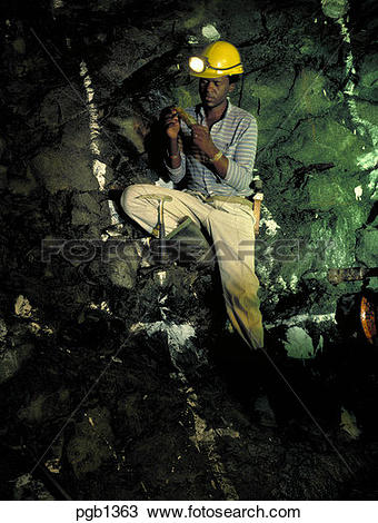 Stock Photo of Geologist examining rock sample at the work face.