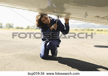 Stock Photo of Female mechanic working on underside of airplane.