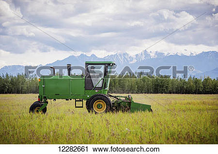 Stock Photography of Self propelled disc mower cutting a field of.