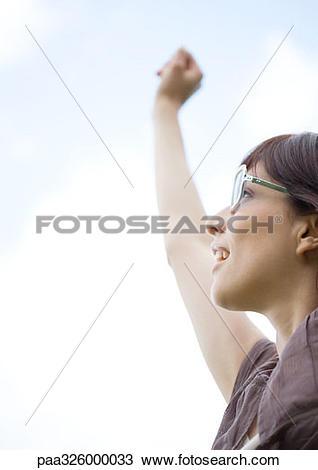 Stock Photo of Woman wearing glasses, reaching arm upward.