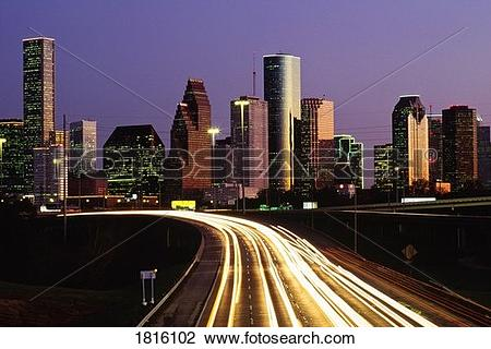 Stock Photo of Streaking car lights at night and downtown Houston.