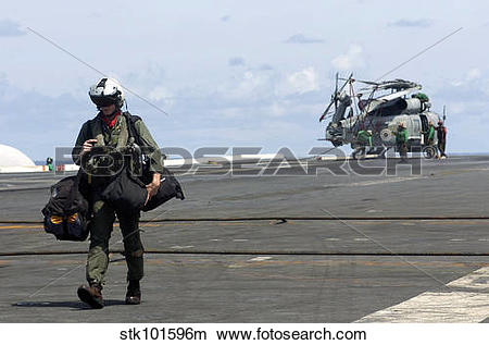 Stock Photo of A pilot walks across the flight deck of USS Kitty.