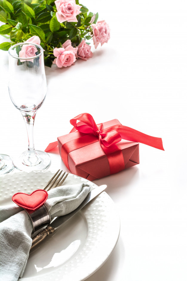 Valentines day dinner with table place setting with red gift.