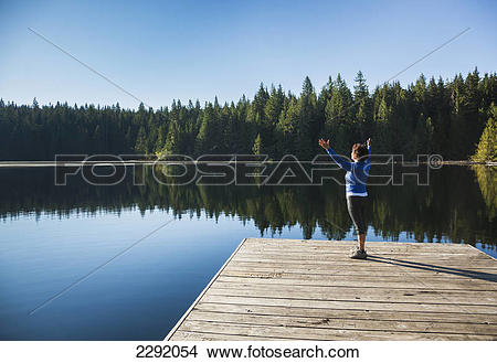 Stock Photo of A woman greets the morning sun on a dock on lizard.