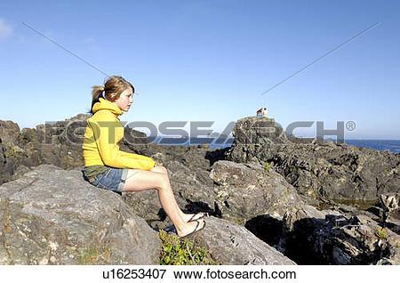 Picture of Teen girl sitting on rocks overlooking Pacific Ocean.