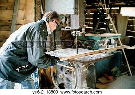 Stock Photography of Carpenter cuts a piece of wood with circular.