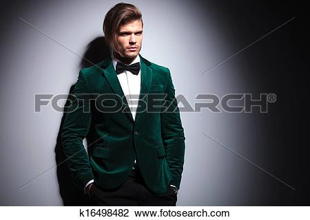 Stock Photo of long haired young man in velvet suit and bow tie.