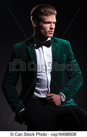 Stock Photography of seated elegant man in green velvet suit.