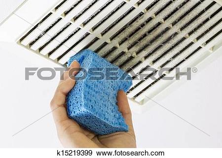 Stock Photograph of Cleaning Bathroom Fan Vent Cover with Sponge.