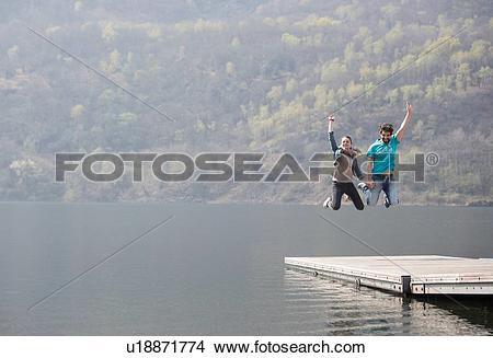 Stock Photo of Young couple jumping mid air on pier at Lake.