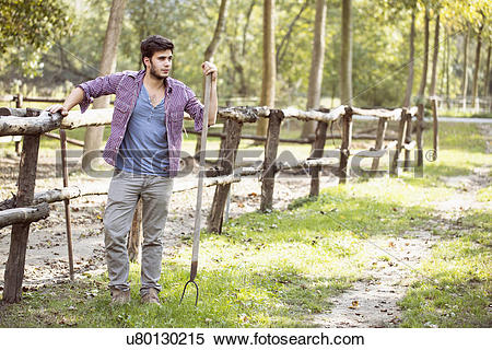 Stock Image of Young male farmer leaning against paddock fence.