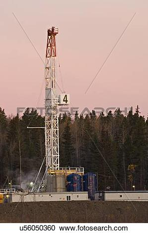 Stock Photography of vertical image land based drill rig sunrise.