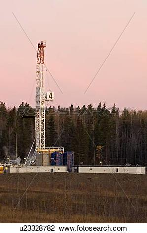 Stock Photo of vertical image land based drill rig sumrise.