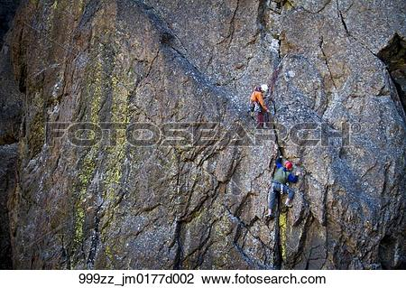 Stock Photo of Two men rock climbing a vertical rock wall on The.
