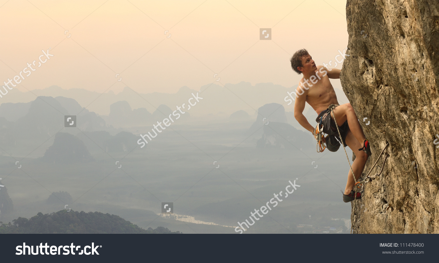 Young Man Climbing Vertical Wall With Valley View On The.