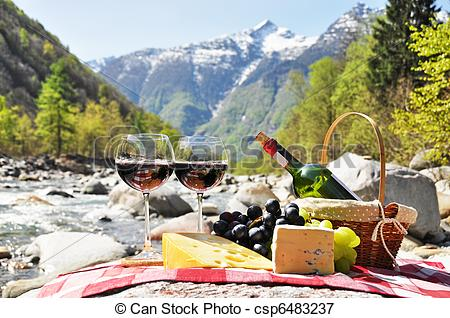 Picture of Red wine, cheese and grapes served at a picnic.