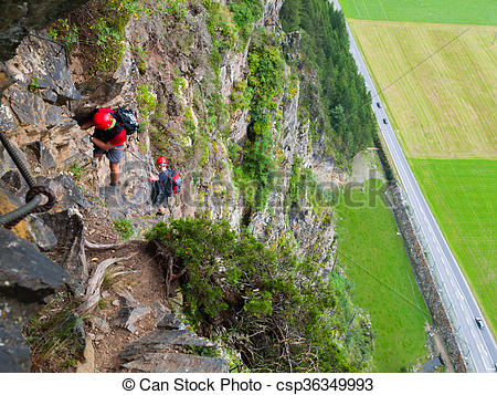 Stock Photographs of Climbers on via ferrata high above road.