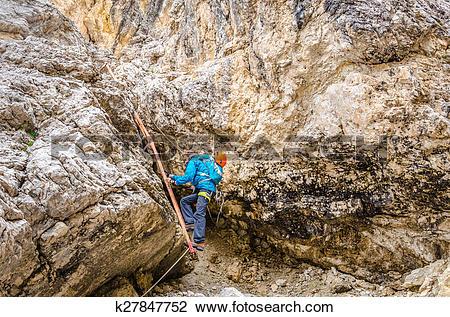 Stock Photo of Woman climbing on metal ladder in via ferrata.
