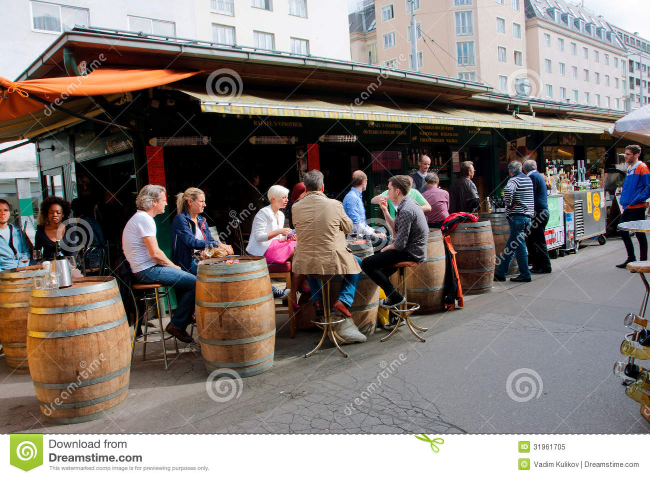People Sit Around The Barrels And Drink Wine Near The Small Wine.