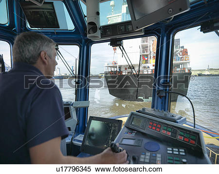 Stock Image of Captain steering tugboat in wheelhouse u17796345.
