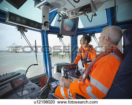 Stock Photography of Tugboat workers in wheelhouse u12198020.