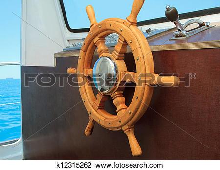 Stock Photo of old ship helm in the wheelhouse k12315262.