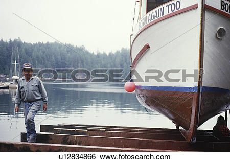 Stock Images of Kyuquot, first nations fisher examines boat hull.