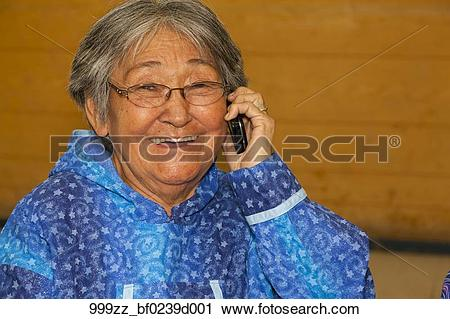 Stock Photography of Elder native woman on cell phone in the.