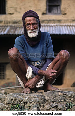 Stock Photography of Siklis village elder squats NEPALI style.