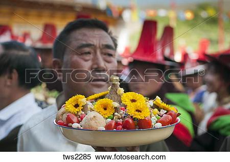 Stock Image of Village elders bring tsampa & other food offerings.