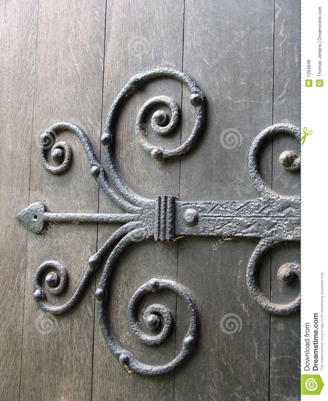Ancient Wrought Iron Ornate Door Hinge On Old Wooden Door