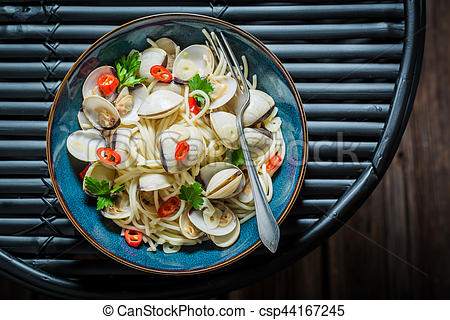 Stock Photo of Enjoy your spaghetti Vongole with clams, parsley.